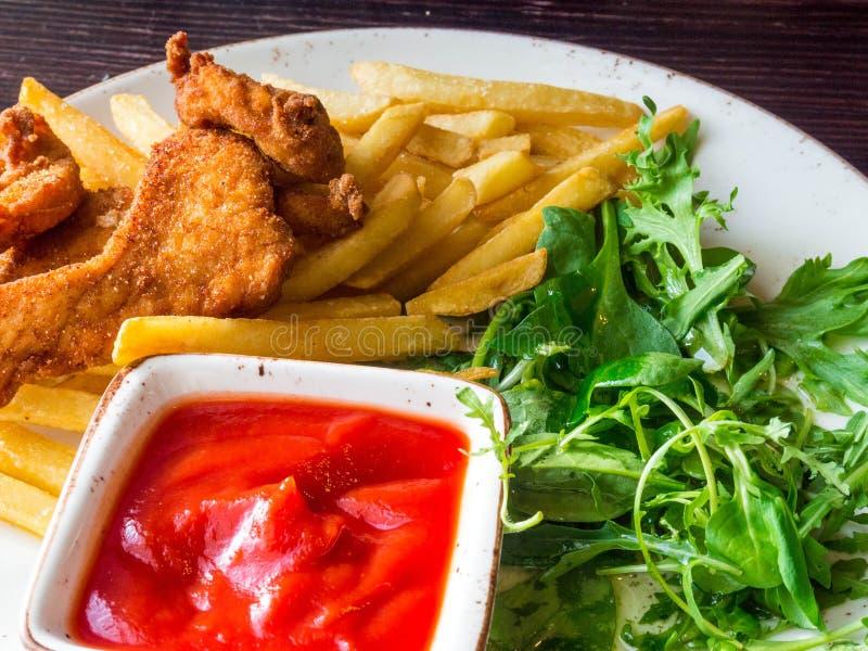 油煎的鸡翅和腿有薯条的在木桌上 与油煎的面包酥脆油煎的肯塔基鸡鲜美晚餐 库存照片