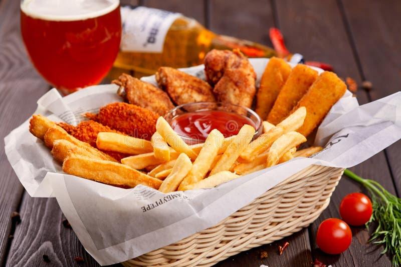 油煎的鸡翅在酥脆上添面包用土豆油炸物 啤酒快餐 免版税库存照片