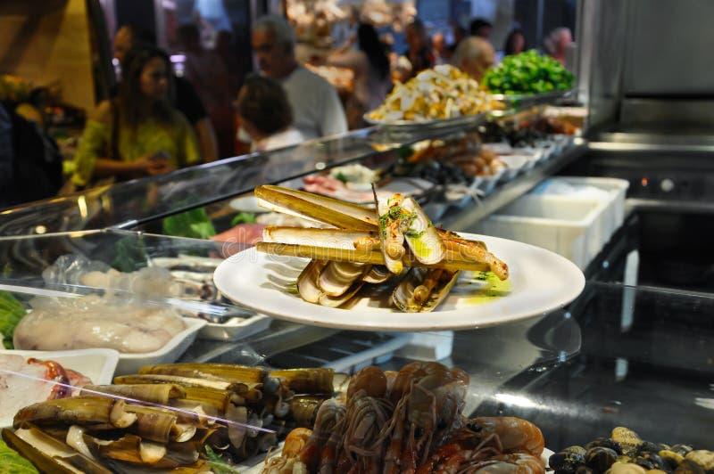 油煎的Gould ` s剃刀壳或Canyut navaja在橄榄油和pesto 虾,竹起重器刀子蛤蜊和淡菜在冰在玻璃加州 免版税库存图片