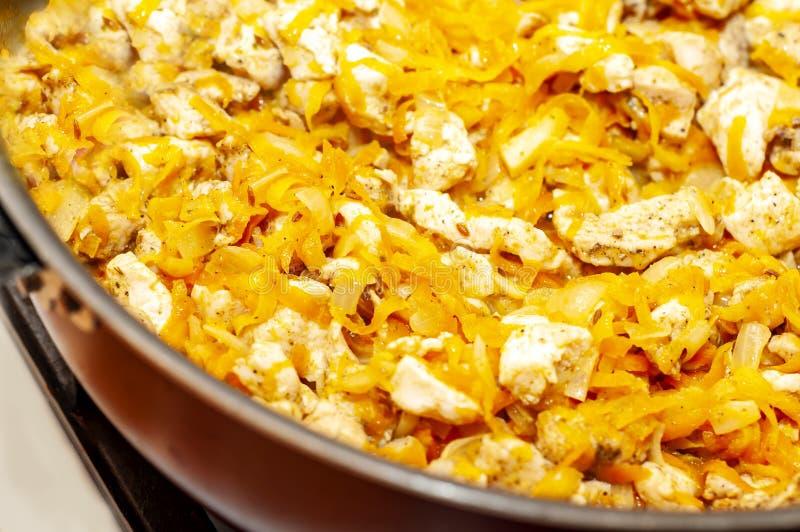 油煎肉的过程用在平底锅的切好的红萝卜 库存图片