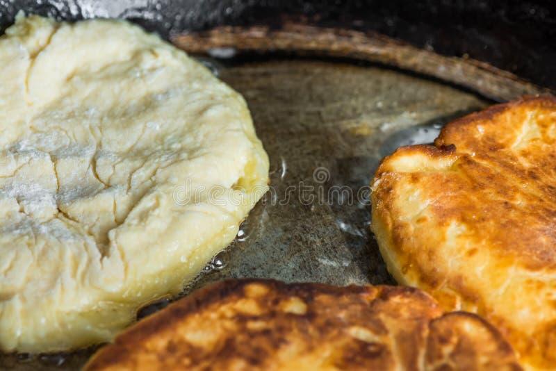 油煎酸奶干酪油炸馅饼或薄煎饼的过程在极热的油在老铁熔铸了平底锅,农村样式 库存照片