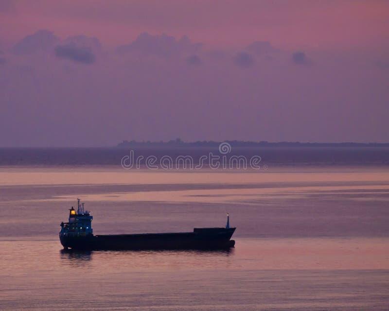 油船剪影停泊了在船锚反对红色日落天空 图库摄影