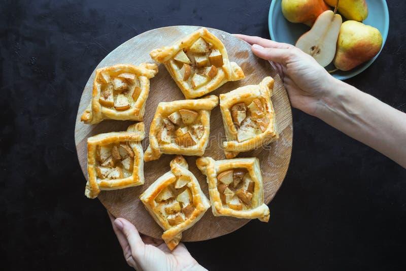 油酥点心饼用在一张黑桌上的梨 自创的蛋糕 顶视图 图库摄影