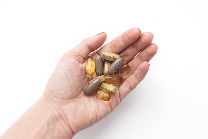 治疗和药房概念 五颜六色的药片在白色背景隔绝的手上 库存照片