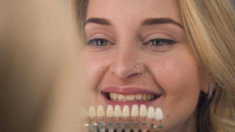 治疗女性耐心妇女牙的牙医被审查在漂白牙医的牙 库存图片