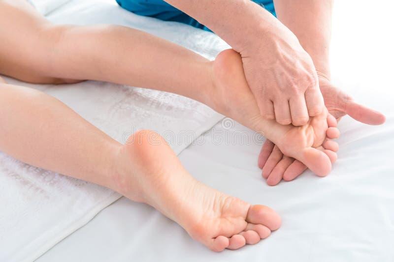 治疗师的手在健康中心做着脚按摩 免版税图库摄影