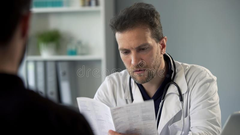 治疗师读书患者做诊断,医疗保健医学的测试结果 免版税库存图片