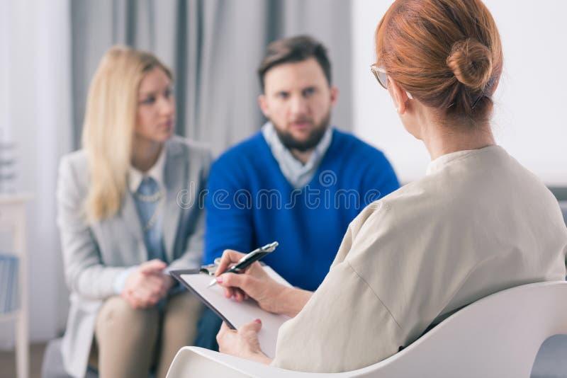 治疗师谈话与一加上问题 免版税库存图片