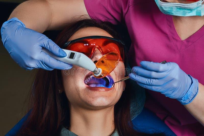 治疗患者的女性牙医 坐在牙医的椅子的年轻女人 免版税库存图片
