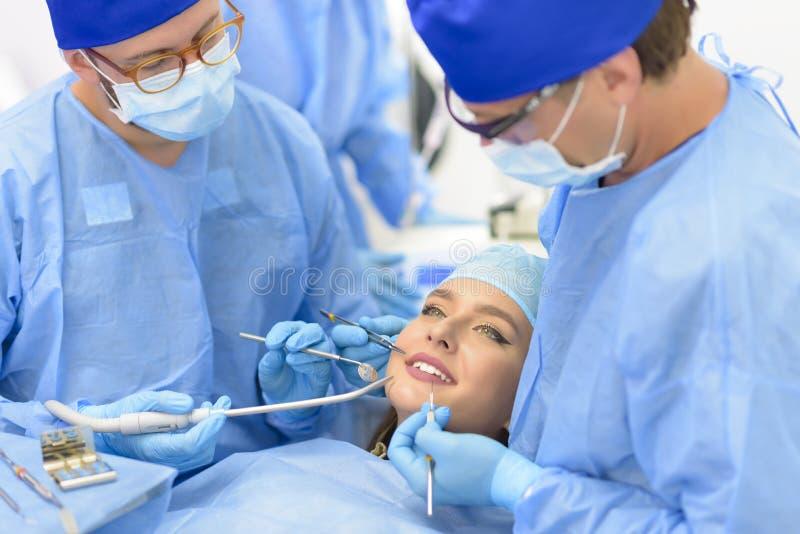 治疗患者的牙医医生和他的队 免版税库存图片