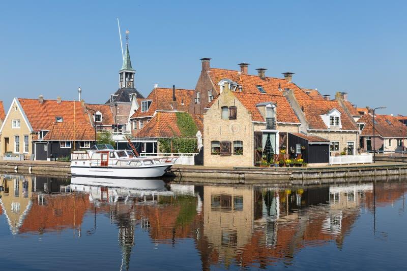 沿一条运河在Makkum,一个老荷兰村庄的议院 图库摄影