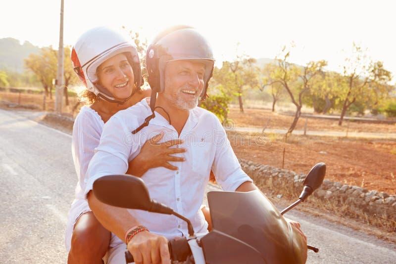 沿乡下公路的成熟夫妇骑马小型摩托车 免版税图库摄影