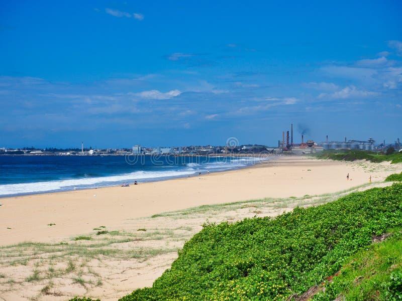 沿伍伦贡海滩对肯布拉港钢厂,澳大利亚的看法 免版税库存图片