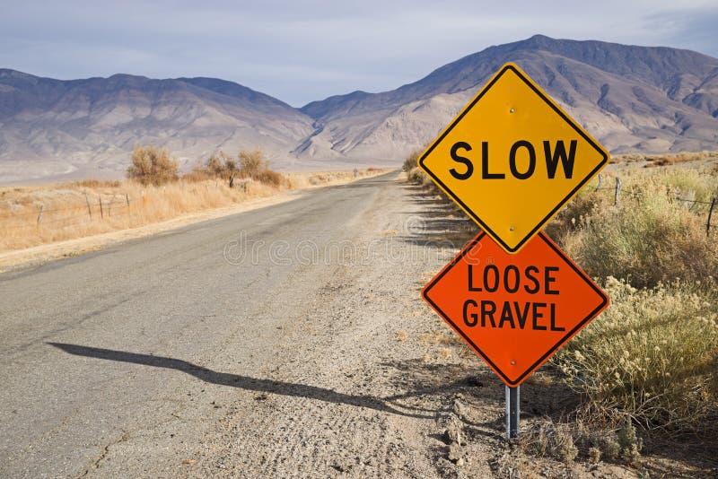 沿农村路的缓慢的宽松石渣标志 库存照片