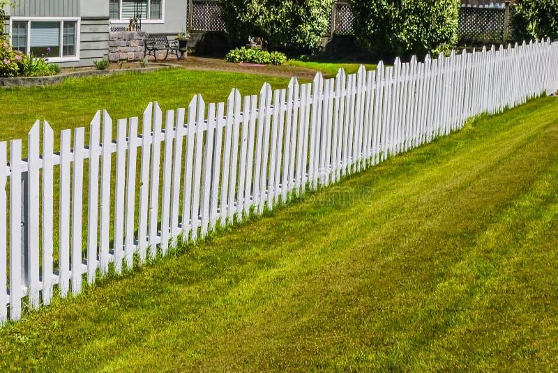 沿前院的白色长的木篱芭住宅房子 库存图片