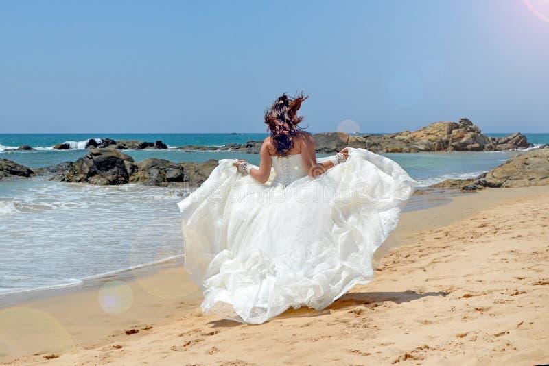 沿含沙海岸线的长发深色的新娘奔跑在石头背景在海,在印度洋的海滩 免版税库存照片