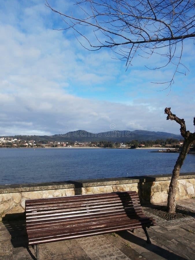沿散步的镇静步行 海滩看见的,坐的长凳 免版税图库摄影