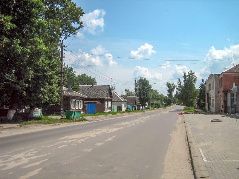 沿村庄与一和二层楼的房子的直接沥青街道 免版税图库摄影