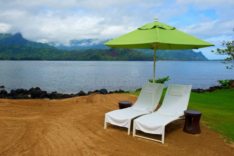 沿椅子海岸线考艾岛疗法伞 库存图片