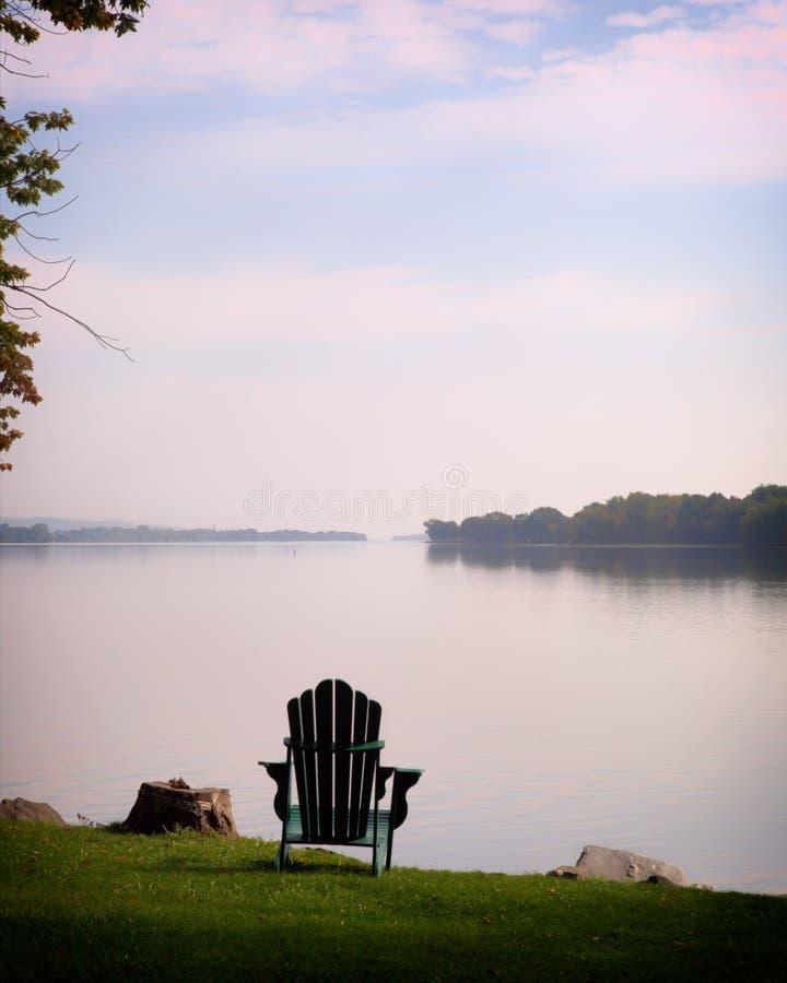 沿河的一把绿色Adirondak椅子 库存图片