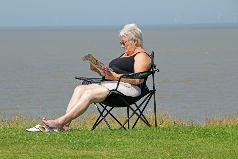 沿海休闲读书 免版税库存图片