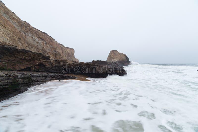 沿海岩石和波浪在海洋靠岸在日出 库存图片