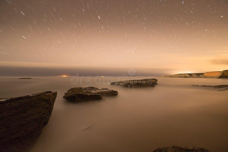 沿海岩石的长的曝光图象在海洋海滩的 库存照片