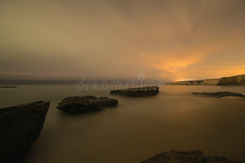 沿海岩石的长的曝光图象在海洋海滩的 免版税库存图片