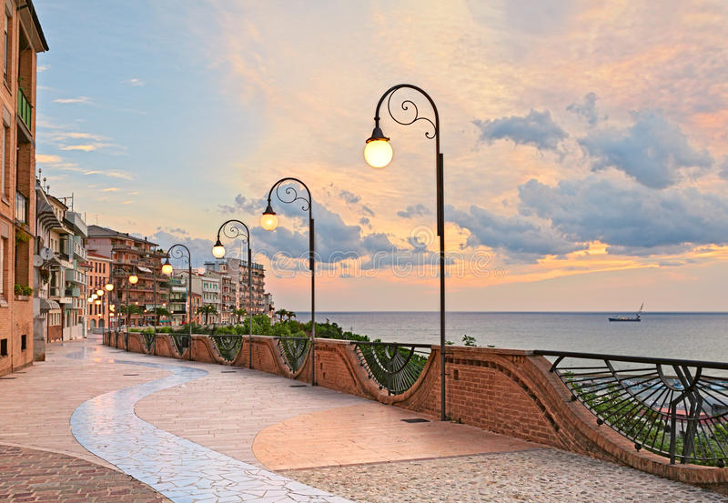 沿海岸区在黎明在奥尔托纳,阿布鲁佐,意大利-与街灯的美丽的大阳台在亚得里亚海 图库摄影