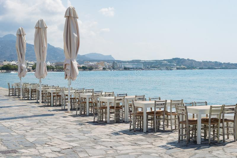 沿海岸区餐馆椅子桌海海景岸海岛,希腊 免版税库存照片