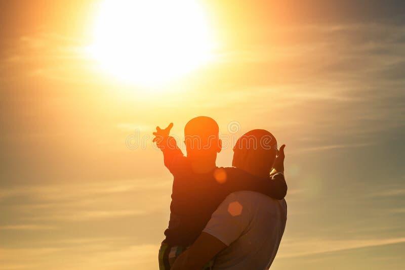 沿海滩在日落,暑假家庭的父亲和儿子步行 免版税库存照片