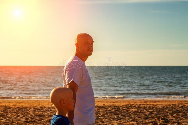 沿海滩在日落,暑假家庭的父亲和儿子步行 免版税库存图片