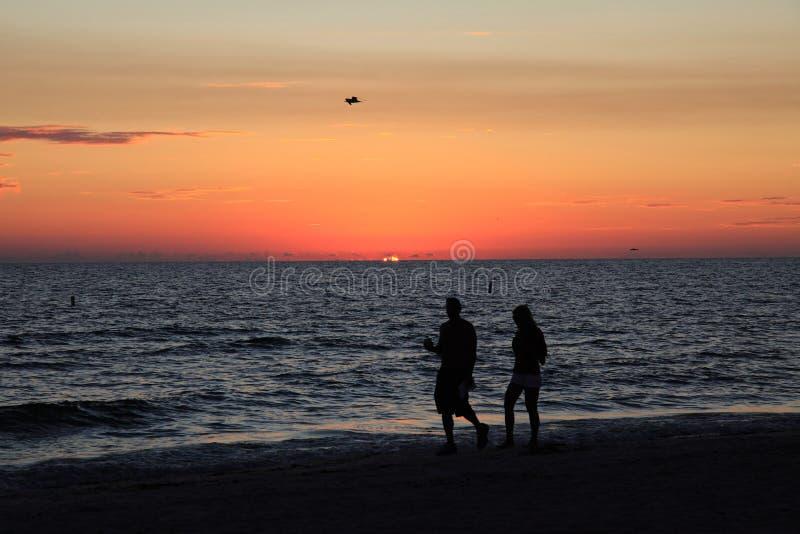 沿海滩夫妇日落走 免版税库存照片