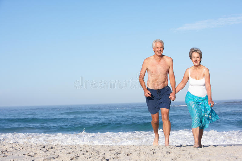 沿海滩夫妇节假日运行的前辈 免版税库存图片