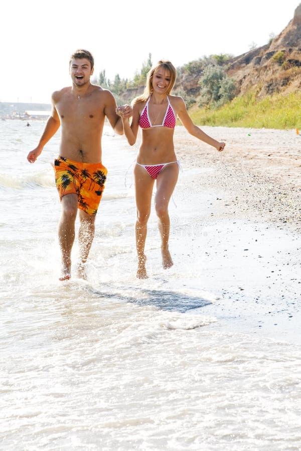 沿海滩夫妇运行的年轻人 库存图片