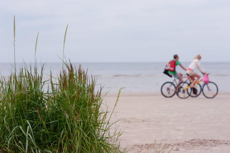 沿海滩自行车夫妇乘驾 免版税图库摄影