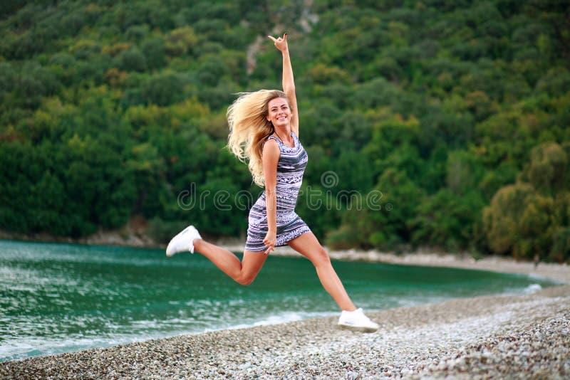 沿海的跳跃的愉快的女孩在绿色森林背景  免版税库存照片