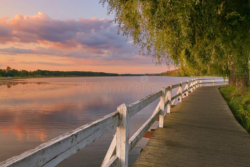 沿湖岸的沃尔什滕,波兰美丽如画的木走道在日落 免版税库存照片