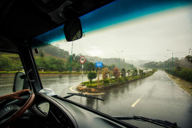 沿热带植物的高速公路在公共汽车窗口外面的大雨下 免版税库存图片