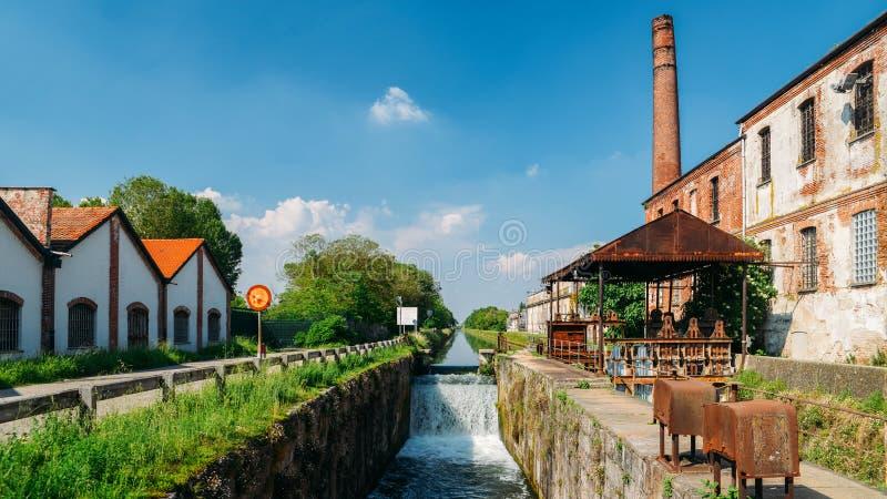 沿着小瀑布的老工业仓库在Naviglio Pavese,用帕尔瓦连接市米兰的运河的一把锁 图库摄影