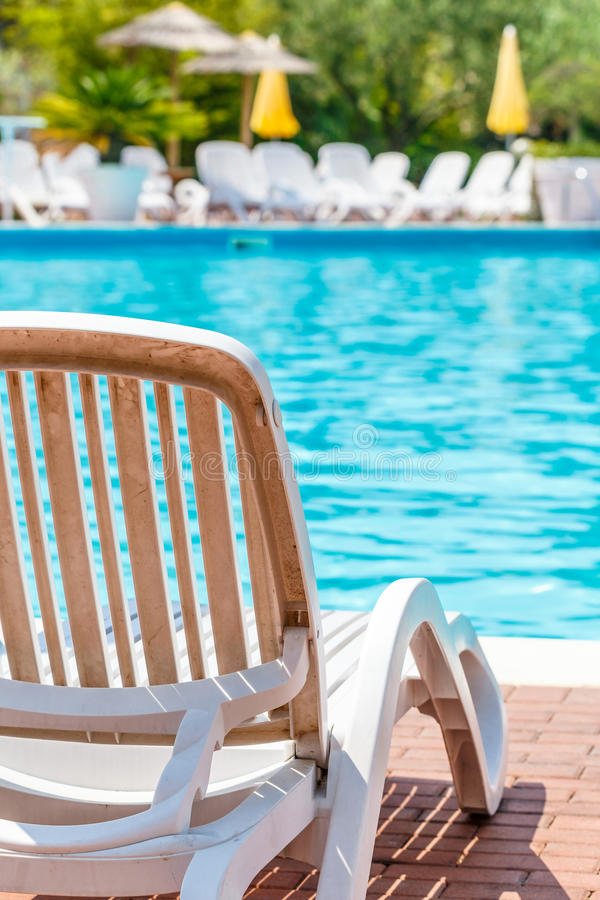 沿着水池的舒适的可躺式椅椅子 免版税库存图片
