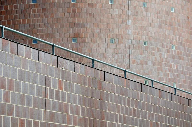 沿着现代大厦弯曲的门面的金属细长立柱  图库摄影