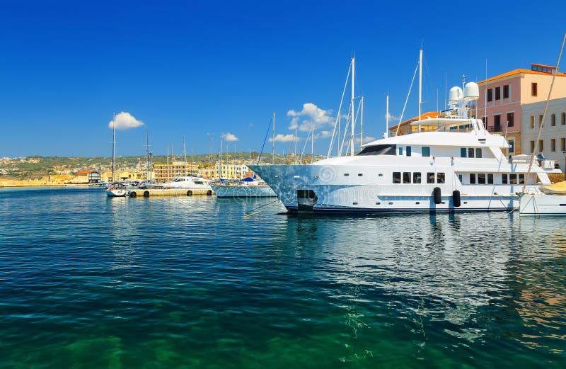 沿着船坞的大白色豪华游艇地中海的,干尼亚州,克利特,希腊 免版税图库摄影