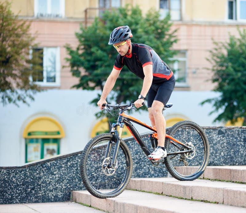 沿着走具体台阶的男性骑自行车者 免版税库存图片
