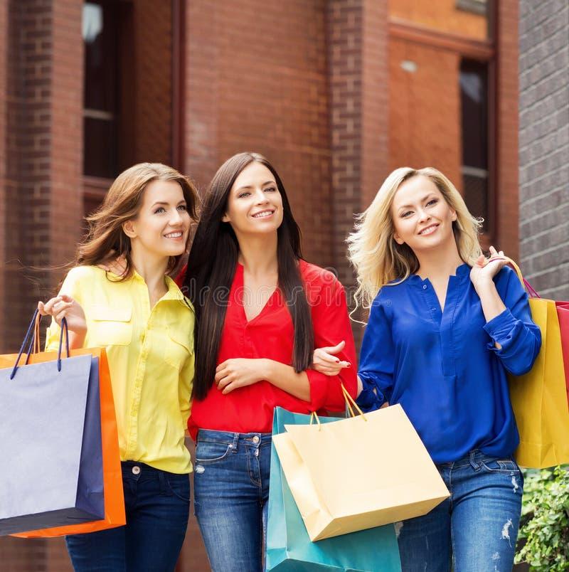 沿着走街道的三名美丽的妇女 库存照片