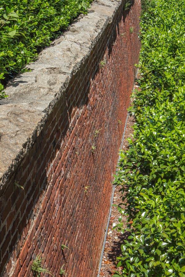 沿着高砖护墙的看法与被下乡的石盖帽,绿色灌木 库存图片