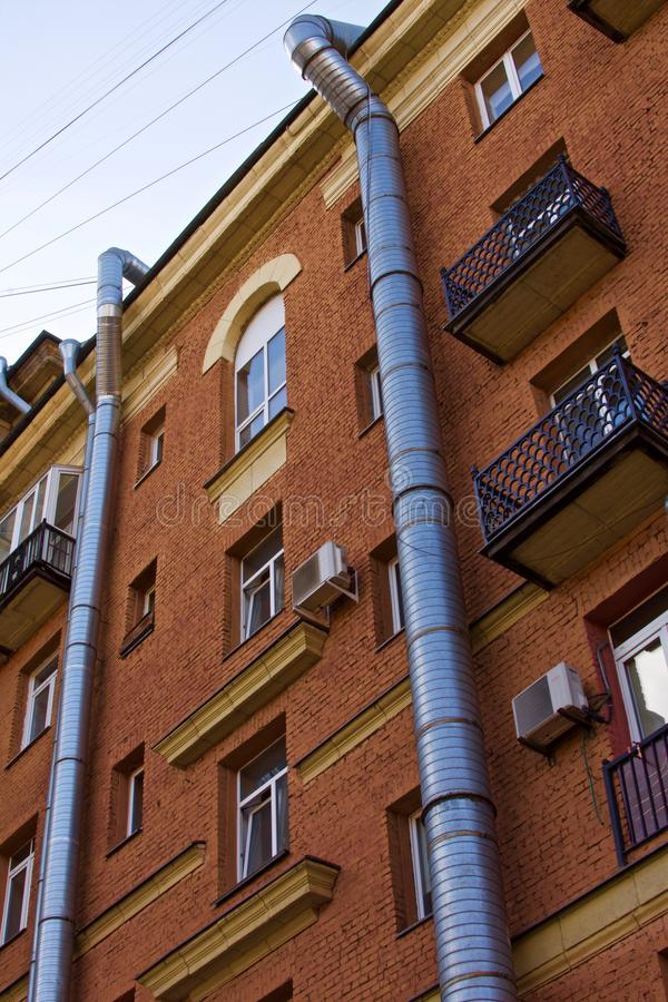 沿砖瓦房的门面跑的两支金属空气通风的管 图库摄影
