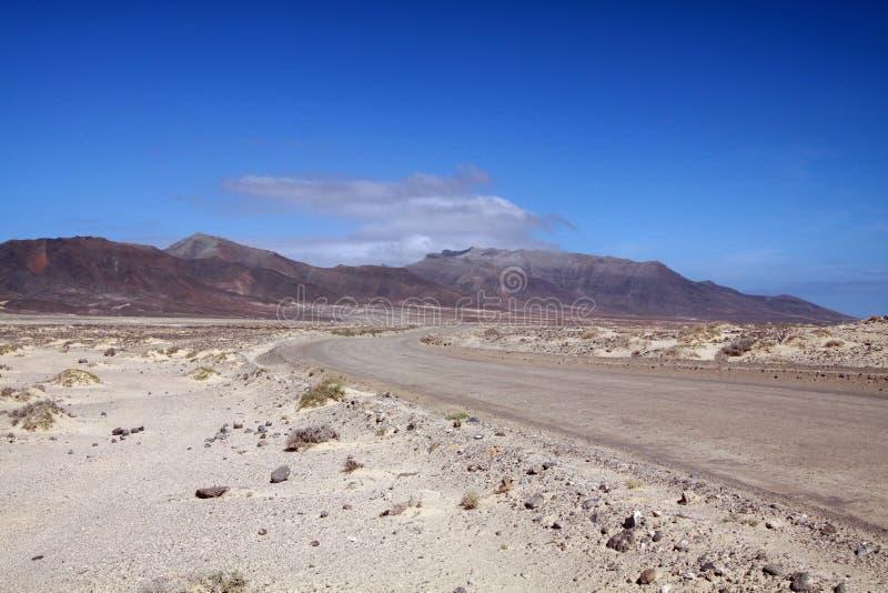 沿西北海岸的土路通过费埃特文图拉岛,加那利群岛光秃的干旱的风景  免版税图库摄影