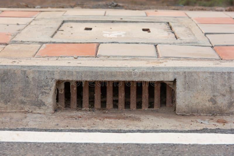 沿路的下水道流失在城市 免版税库存图片