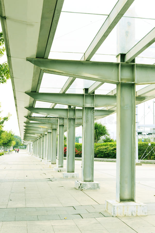 沿路面或边路的现代长的雨走廊在城市街道一边 库存照片